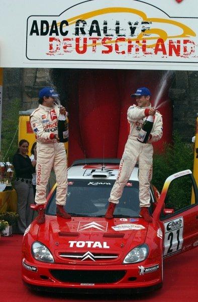 Rallye Deutschland winners Daniel Elena (FRA), left, and Sebastien Loeb (FRA), Citroen,  spray the victory champagne.Fia World Rally Championship, Rd10, Rallye Deutschland, Germany, Leg 3, 25 August 2002.DIGITAL IMAGE