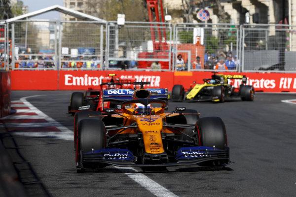 Carlos Sainz Jr., McLaren MCL34, leads Charles Leclerc, Ferrari SF90, and Daniel Ricciardo, Renault R.S.19