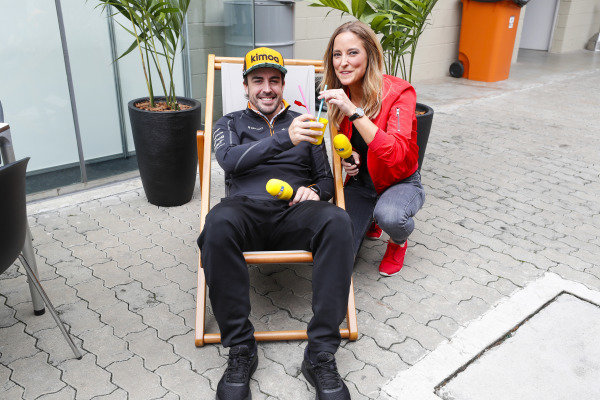 Fernando Alonso, McLaren, holds a drink while sitting on a deckchair next to RTL presenter Anna Fleischhauer.