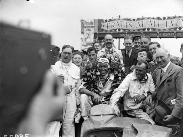 Cyril Whitcroft, 1st position, sits on his Riley Brooklands 9 after the race. George Eyston, 2nd position, stands on the left of frame.