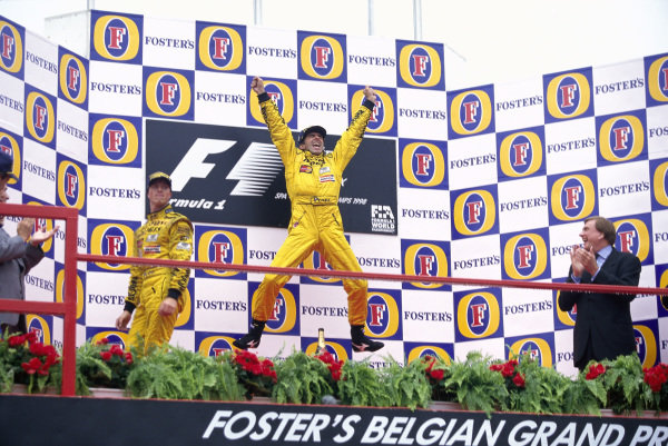 Damon Hill, 1st position, celebrates on the podium while teammate Ralf Schumacher, 2nd position, looks on.