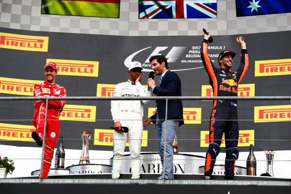 Spa Francorchamps, Belgium.  Sunday 27 August 2017. Mark Webber, Channel 4 F1, interviews winner Lewis Hamilton, Mercedes AMG, 1st Position, on the podium alongside Sebastian Vettel, Ferrari, 2nd Position, and Daniel Ricciardo, Red Bull Racing, 3rd Position. World Copyright: Sam Bloxham/LAT Images  ref: Digital Image _J6I0285