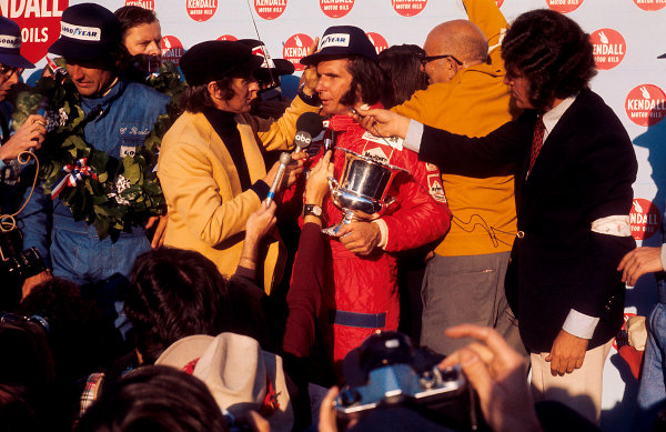 1974 United States Grand Prix East. Watkins Glen, New York, USA. 4th - 6th October 1974. New drivers world champion Emerson Fittipaldi celebrates taking his second world title, here being interviewed by the outgoing champion Jackie Stewart. Race winner Carlos Reutemann (Brabham Ford) 1st position is to the left of him on the podium, portrait.  World Copyright: LAT Photographic. Ref:  74USA04.