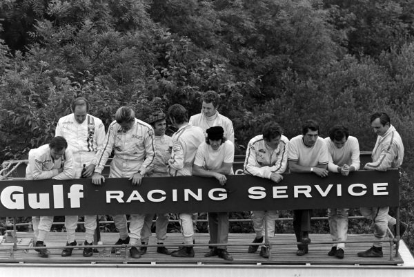 Drivers stand behind a Gulf Racing Service sign. L-R: Bruce McLaren, Denny Hulme, Graham Hill, Silvio Moser, Jo Siffert, Piers Courage, Jackie Stewart, Jochen Rindt, Vic Elford, Jean-Pierre Beltoise, and Chris Amon.