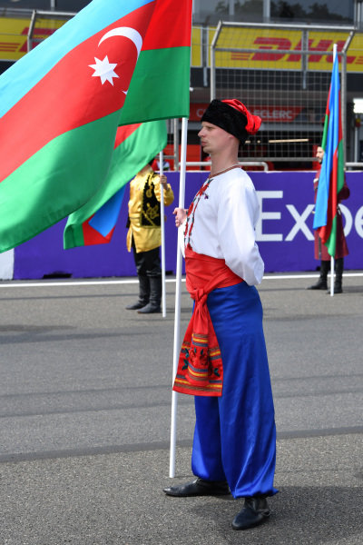 A flag holder in national costume on the grid