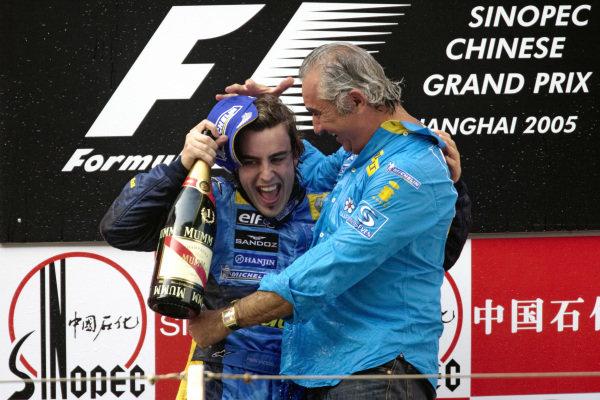 Fernando Alonso celebrates victory and the constructors' championship title on the podium with Flavio Briatore.