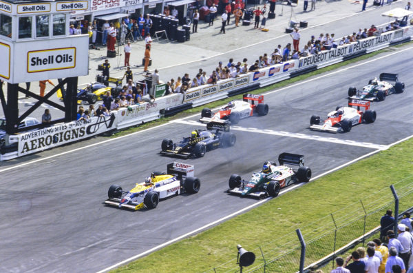 Nigel Mansell, Williams FW11 Honda, leads Gerhard Berger, Benetton B186 BMW, Ayrton Senna, Lotus 98T Renault, Keke Rosberg, McLaren MP4-2C TAG, Alain Prost, McLaren MP4-2C TAG, and Teo Fabi, Benetton B186 BMW, at the start.