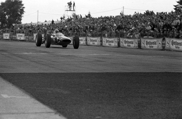 John Surtees, Ferrari 158, celebrates as he crosses the finish line for victory.