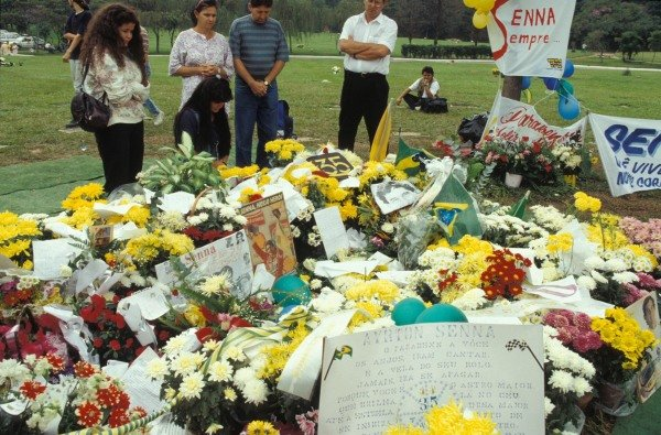 Fans gather and lay flowers on the grave of Ayrton Senna.