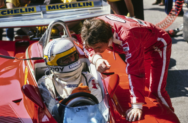 Gilles Villeneuve talks with team mate Jody Scheckter who is seated in his Ferrari 312T4.