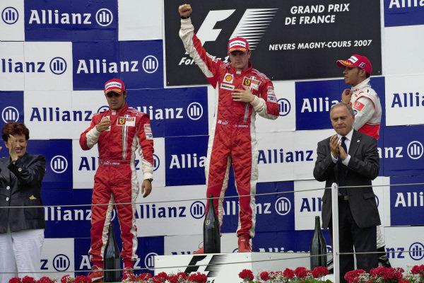 Kimi Räikkönen celebrates victory on the podium with teammate Felipe Massa, 2nd position, and Lewis Hamilton, 3rd position.