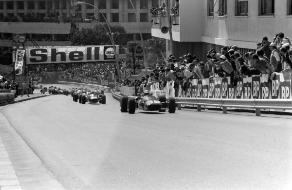 Lorenzo Bandini, Ferrari 312, leads Jack Brabham, Brabham BT19 Repco, and the rest of the field up Beau Rivage at the start.