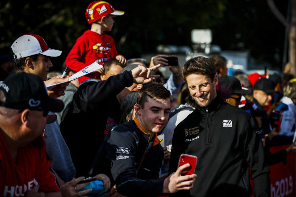 Romain Grosjean, Haas F1 Team poses for a selfie with a fan at the Federation Square event