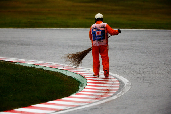 Suzuka Circuit, Japan. Friday 06 October 2017. A Marshal sweeps water of a kerb. World Copyright: Andy Hone/LAT Images  ref: Digital Image _ONZ2022
