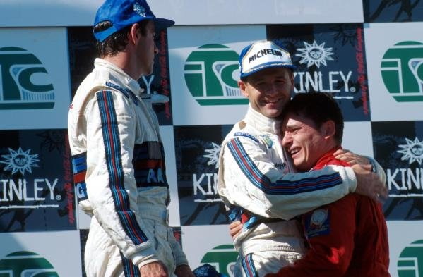 An emotional third place finisher Giancarlo Fisichella (ITA) Alfa Romeo is hugged by second place finisher Nicola Larini ITA) Alfa Romeo, whilst race winner Alessandro Nannini (ITA) Alfa Romeo looks on. 