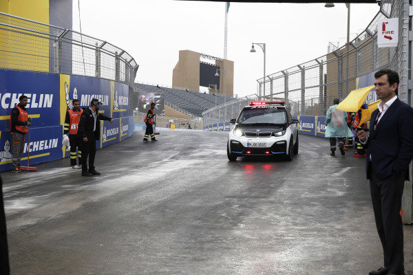 Race Director Scot Elkins performs an exploratory lap of the track as marshalls sweep up the standing water