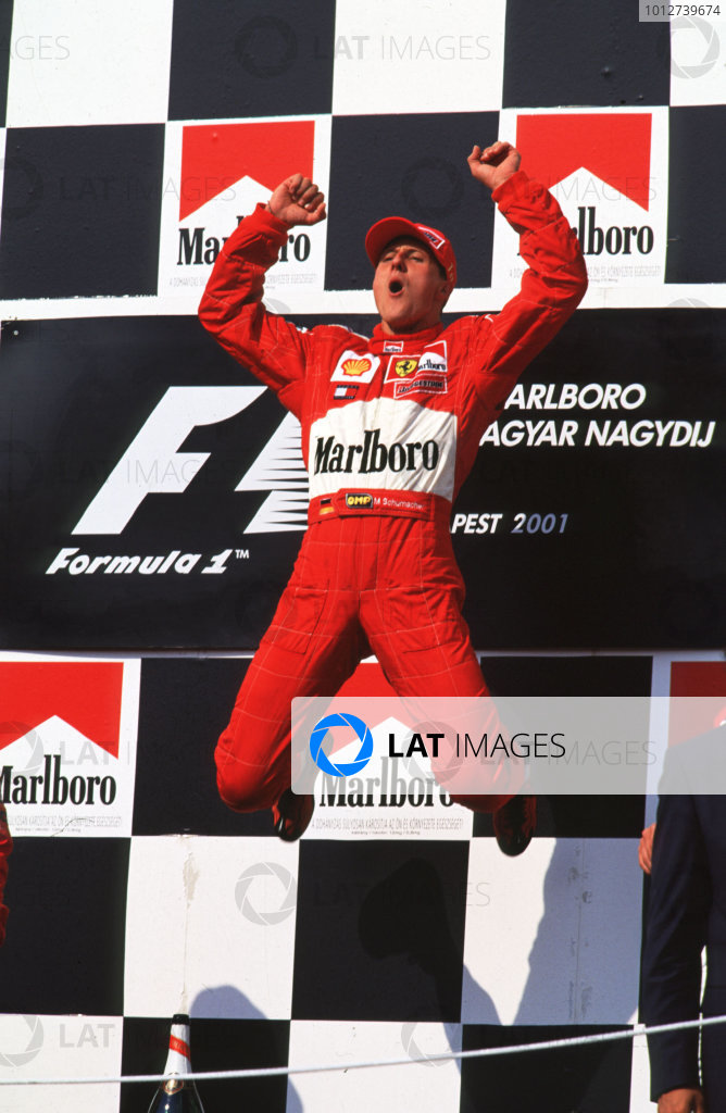 2001 Hungarian Grand Prix. Hungargoring, Budapest, Hungary. 17-19 August 2001. Race winner Michael Schumacher, Ferrari F2001 jumps in the air in joy after clinching 4th World driver championship, and Ferrari's 3rd consecutive constructors title. Podium. World Copyright: Charles Coates/ LAT Photographic ref: 35mm Image A21