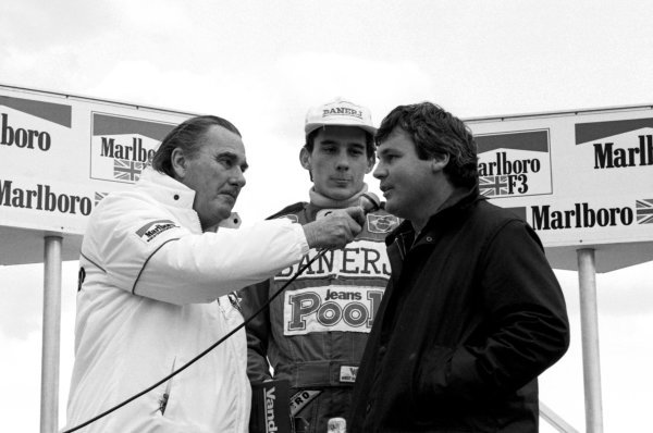 Race winner Ayrton Senna (BRA) West Surrey Racing on the podium as Williams F1 driver Alan Jones (AUS) is interviewed. British Formula Three Championship, Silverstone, England, 20 March 1983.