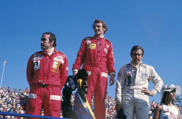 Clay Reggazoni, 3rd position, Niki Lauda, 1st position, and Carlos Reutemann, 2nd position, on the podium.