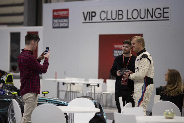 Ari Vatanen poses for a photograph with a fan in the VIP Club Lounge