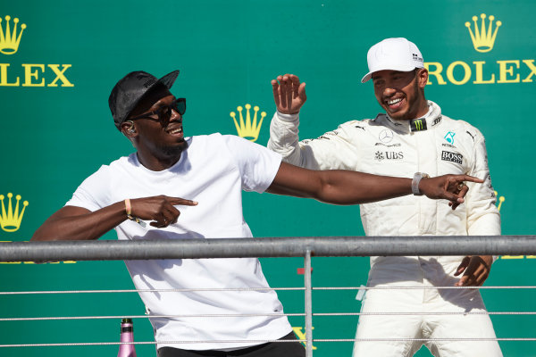 Circuit of the Americas, Austin, Texas, United States of America. Sunday 22 October 2017. Usain Bolt performs his trademark lightning bolt pose with Lewis Hamilton, Mercedes AMG, 1st Position, on the podium. World Copyright: Steve Etherington/LAT Images  ref: Digital Image SNE19801