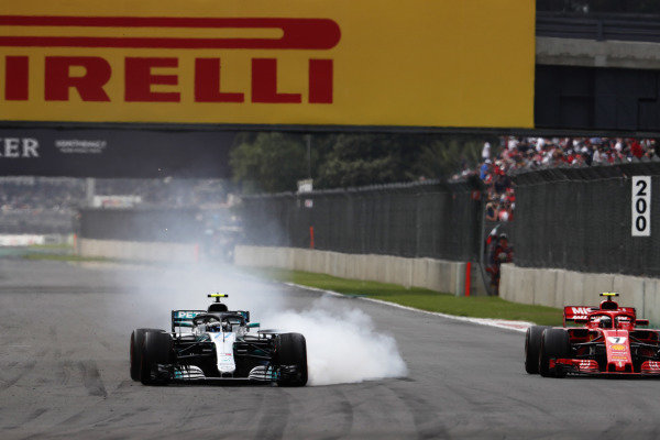 Valtteri Bottas, Mercedes AMG F1 W09 EQ Power+, locks his brakes whilst battling with Kimi Raikkonen, Ferrari SF71H