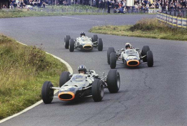 Graham Hill, BRM P261, leads Jackie Stewart, BRM P261, and Dan Gurney, Brabham BT11 Climax.