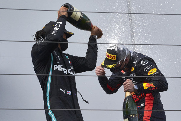 Lewis Hamilton, Mercedes-AMG Petronas F1, 1st position, sprays Max Verstappen, Red Bull Racing, 2nd position, with Champagne on the podium