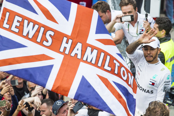 Lewis Hamilton, Mercedes AMG F1, waves to fans next to a Union Flag.