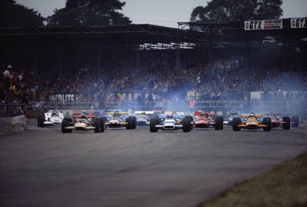 Jochen Rindt, Lotus 49B Ford (left), Jackie Stewart, Matra MS80 Ford (centre), and Denny Hulme, McLaren M7A Ford (right), lead the rest of the field at the start.