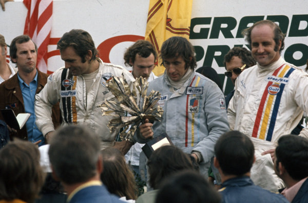 Winner Jackie Stewart holds his trophy on the podium alongside Peter Revson, 2nd position, and Denny Hulme, 3rd position.