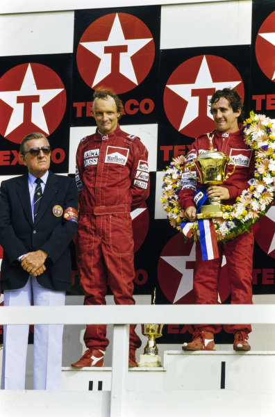 Alain Prost, 1st position, Niki Lauda, 2nd position, and Jean-Marie Balestre on the podium.