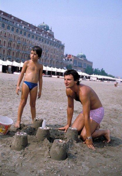 Lido di Venezia, or Venice Lido, Italy. 1983 Riccardo Patrese on the beach with his son Simone