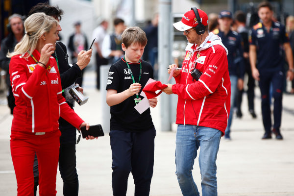 Silverstone, Northamptonshire, UK.  Sunday 16 July 2017. Sebastian Vettel, Ferrari, signs an autograph for a young fan. World Copyright: Andy Hone/LAT Images  ref: Digital Image _ONY7543
