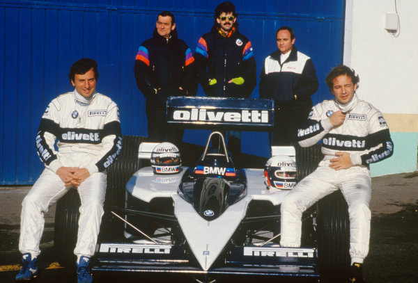 Riccardo Patrese and Elio de Angelis, sit on the tyres of the new Brabham BT55 with Ron Tauranac and Gordon Murray standing behind, portrait. 