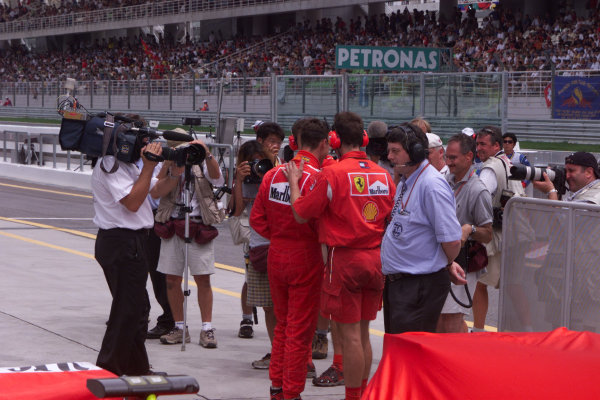 Sepang, Kuala Lumpur, Malaysia.20-22 October 2000.Mechanics congratulate Michael Schumacher (Ferrari) on qualifying on pole position, in parc ferme at the end of the session. The media swarms around him to capture the moment. ref: digital imageWorld Copyright - LAT Photographic
