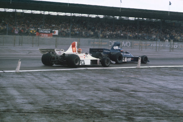 Silverstone, England. 17-19 July 1975. Patrick Depailler, Tyrrell 007 Ford, leads Tony Brise, Hill GH1 Ford. Ref: 75GB26. World Copyright - LAT Photographic