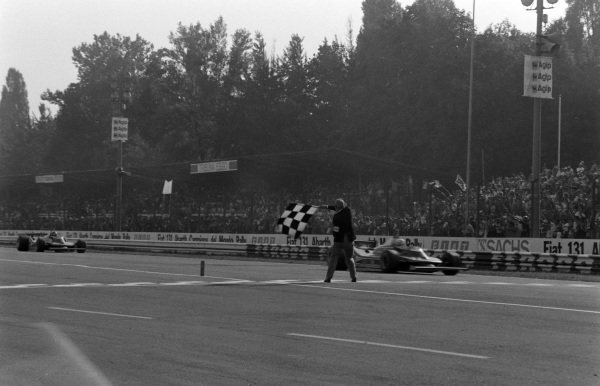 Jody Scheckter, Ferrari 312T4, raises his arm in the air as he takes the chequered flag to win the race and secure his maiden world championship. Team-mate Gilles Villeneuve follows closely behind in second.