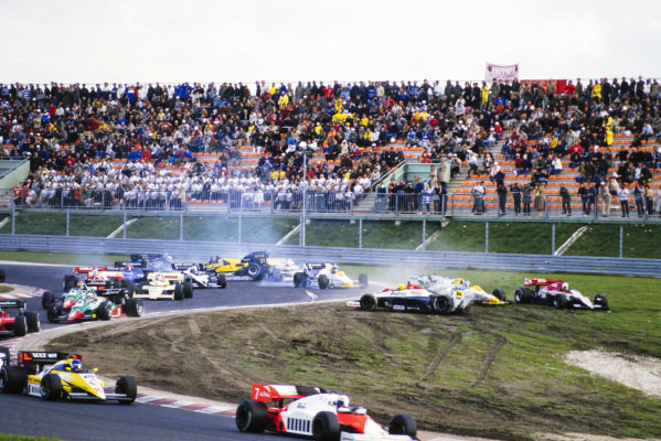 Andrea de Cesaris, Ligier JS23B Renault, cuts across the grass to avoid the carnage caused by Ayrton Senna, Toleman TG184 Hart, colliding with Keke Rosberg, Williams FW09B Honda. Further back, Gerhard Berger, ATS D7 BMW, gets airborne after crashing with Jacques Laffite, Williams FW09B Honda, and Marc Surer, Arrows A7 BMW, prompting Nigel Mansell, Lotus 95T Renault, to take avoiding action.