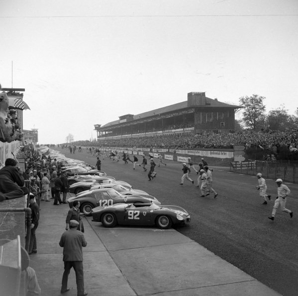 The drivers run to their cars at the start.