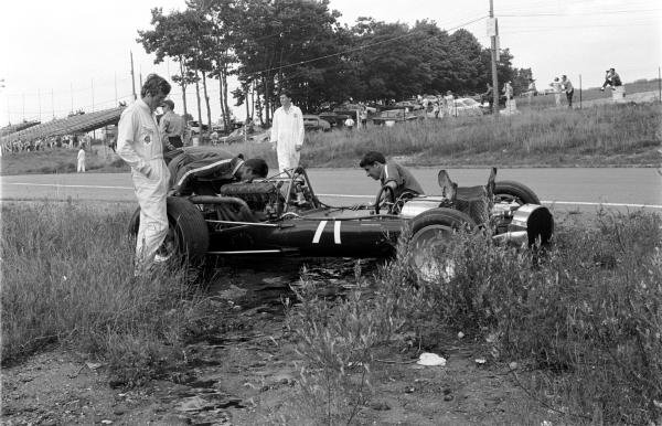 Jochen Rindt (AUT), left, looks on as mechanics inspect the damage to his Cooper-Maserati T81.