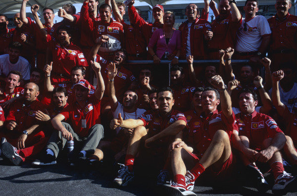 Sepang, Kuala Lumpur, Malaysia. 15-17 October 1999. Eddie Irvine (front) celebrates his 1st position with the Ferrari team and team mate Michael Schumacher (with wife Corinna). Ref: 99MAL64. World Copyright - LAT Photographic