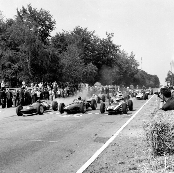 Rouen-les-Essarts, France. 6-8 July 1962. Poleman Jim Clark (Lotus 25 Climax) smokes up his rears as he leads away from Graham Hill (BRM P57) and Bruce McLaren (Cooper T60 Climax) on the grid at the start.  Ref-14563. World Copyright - LAT Photographic
