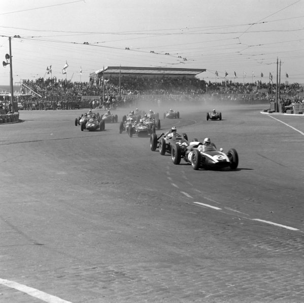 Jack Brabham, Cooper T53 Climax, leads Dan Gurney, BRM P48, as the rest of the field follow behind.