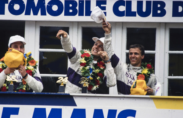 Jan Lammers, Johnny Dumfries and Andy Wallace celebrate victory on the podium.