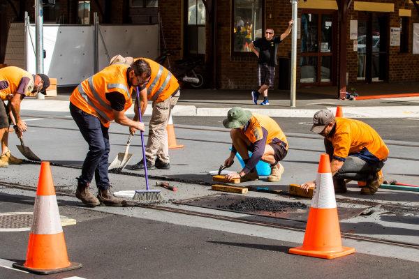 workers installing bitumen over tram tracks
