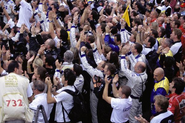 BMW Williams mechanics celebrate victory below the podium.