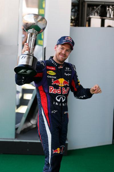 Suzuka Circuit, Suzuka, Japan.  Sunday 13th October 2013. Sebastian Vettel, Red Bull Racing, 1st position, leaves the podium with his trophy.   World Copyright: Steven Tee/LAT Photographic  ref: Digital Image _C3I1226