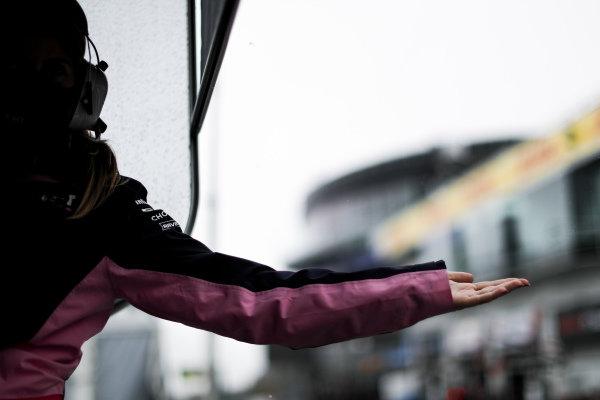 A Racing Point team member checks the rain fall