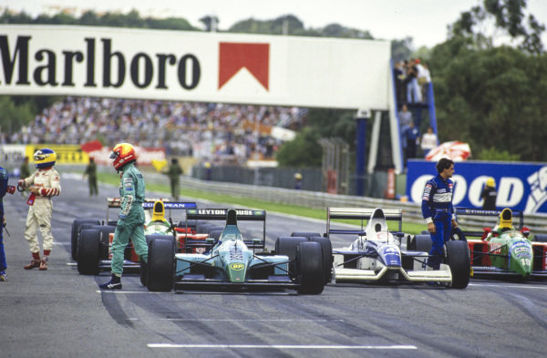 Michele Alboreto, Mauricio Gugelmin, and Jean Alesi abandon their cars on the pit straight during the red flag period.